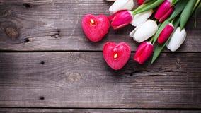 2 красных горящих свечи в форме сердца и яркой весны Стоковая Фотография