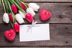 2 красных горящих свечи в форме сердца, пустой бирки и brigh Стоковое Изображение