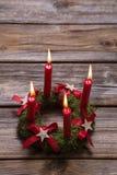 4 красных горящих свечи пришествия на деревянной предпосылке для christm Стоковые Фото