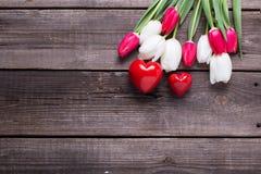 2 красных декоративных сердца и ярких тюльпаны цветут на постаретом w Стоковое Фото