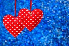 2 красных зашитых сердца вися против голубой предпосылки Стоковое Изображение RF