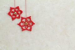 2 красных звезды рождества вязания крючком на помытой губкой предпосылке Стоковые Фото