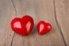 2 красных каменных сердца на деревянной поверхности Стоковая Фотография