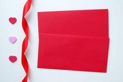 2 красных конверта с сердцами и лента на день ` s валентинки Стоковые Фотографии RF