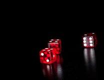 3 красных кости на старой деревянной черной таблице с космосом для текста Стоковое фото RF