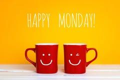 2 красных кружки кофе с усмехаясь стороны на желтой предпосылке Стоковое Изображение