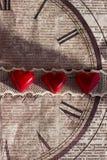 3 красных помадки в форме сердца на ленте шнурка на старой декоративной бумаге Стоковая Фотография