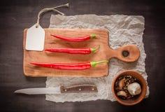 3 красных свежих и острых перца на разделочной доске Темная предпосылка Стоковое фото RF
