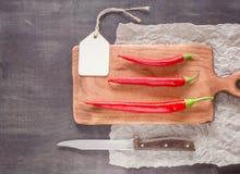 3 красных свежих и острых перца на разделочной доске Темная предпосылка Стоковые Изображения