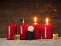 4 красных свечи на деревянной предпосылке Стоковое Фото
