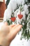 2 красных сердца и руки ткани на тяжелой снежной предпосылке ветви ели, около дома красного кирпича Веселое рождество, С Новым Го стоковые изображения