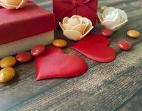 2 красных сердца на деревянной предпосылке, красной коробке, романтичной, шариках Стоковые Фото