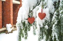 2 красных сердца ткани вися на тяжелой снежной ветви ели, около дома красного кирпича Веселое рождество, С Новым Годом! и Валента стоковое фото rf