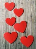 6 красных сердец на древесине стоковые изображения
