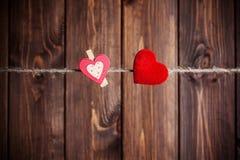 2 красных сердца вися на веревке для белья Стоковые Изображения RF