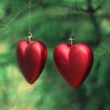 2 красных сердца вися на рождественской елке Стоковое Фото