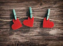 3 красных сердца вися на шнуре на деревянной предпосылке Стоковая Фотография