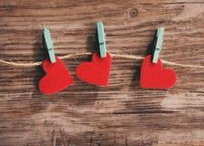 3 красных сердца вися на шнуре на деревянной предпосылке Стоковые Фото