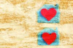 2 красных сердца в ложе на скомканной желтой бумаге Романтичная праздничная карточка Стоковые Фото