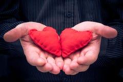 2 красных сердца держали мужские руки Стоковые Изображения RF