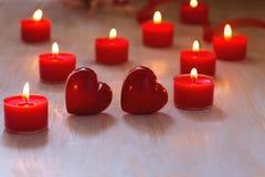 2 красных сердца и горящих свечи на таблице Стоковые Изображения RF