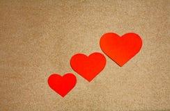 3 красных сердца над бумагой ремесла с космосом экземпляра Стоковое Фото