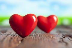 2 красных сердца на деревянной предпосылке Стоковое Изображение