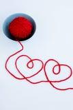 2 красных сердца сделанного от пряжи, шарика пряжи красного цвета и плиты Стоковое фото RF