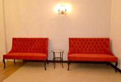 2 красных софы стоят на стене в гостиной Стоковое Изображение