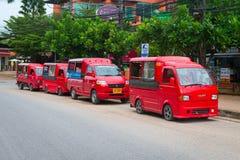 4 красных такси припаркованного в улице Стоковое фото RF