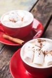 2 красных чашки горячего шоколада или какао на таблице стоковое изображение