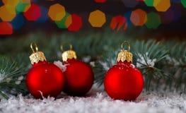3 красных шарика над запачканной предпосылкой светов с ветвью ели Новый Год украшения рождества Стоковое Изображение RF