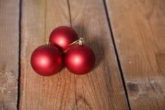 3 красных шарика рождества над деревянной предпосылкой Стоковые Изображения RF