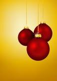 3 красных шарика рождества вися перед желтым золотом Стоковое Изображение