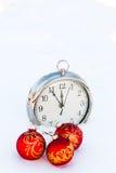 3 красных шарики и часа рождества на снеге Стоковое фото RF