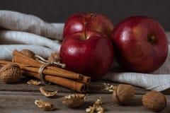3 красных яблоки, ручки циннамона и грецкого ореха на linen салфетке Стоковая Фотография