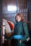 Красн-с волосами девушка держа белую лошадь Стоковое Изображение