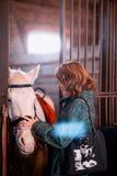 Красн-с волосами девушка держа белую лошадь Стоковая Фотография