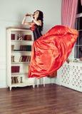 Красота в средний-воздухе Полнометражная съемка студии привлекательной молодой женщины в оранжевом платье завиша в воздухе и игра Стоковые Изображения RF