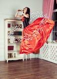 Красота в средний-воздухе Полнометражная съемка студии привлекательной молодой женщины в оранжевом платье завиша в воздухе и игра Стоковое Изображение