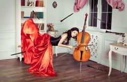 Красота в средний-воздухе Полнометражная съемка студии привлекательной молодой женщины в оранжевом платье завиша в воздухе и игра Стоковое фото RF