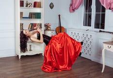 Красота в средний-воздухе Полнометражная съемка студии привлекательной молодой женщины в оранжевом платье завиша в воздухе и игра Стоковые Изображения