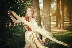 Красота девушки в древесине с тканью на ветре Стоковые Фото