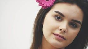 Красота маленькой девочки, чистая кожа, красивый макияж, с длинными черными волосами и пурпурным цветком в ее волосах видеоматериал