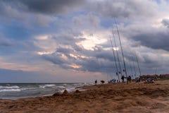 Красота облаков на темном после полудня сопровождает рекреационные рыболовов на пляжах Барселоны Стоковое фото RF