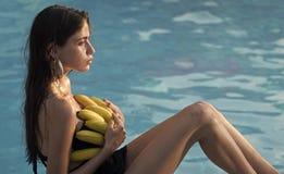Красота стороны женщины Женщина ослабляет в бассейне курорта женщина с тропическим плодоовощ в бассейне Витамин в банане на девуш Стоковая Фотография