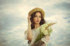 Красота стороны женщины Красота стороны женщины Женщина с цветками облачным небом, красотой Стоковая Фотография RF