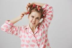 Красота требует поддачи Молодая girly девушка в милых pyjamas принимая дискомфорт волос-curlers, хмуриться и чувствовать или стоковое изображение rf