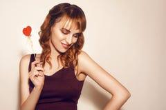 Красота удивила молодую девушку фотомодели с печеньем сердца Валентайн форменным в руке Любовь красивейшие детеныши женщины стоковое фото