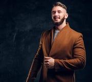 Красота ` s людей, сезонная мода Стильно одетый человек в пальто demi-сезона усмехаясь и выглядя косой Фото студии стоковые изображения